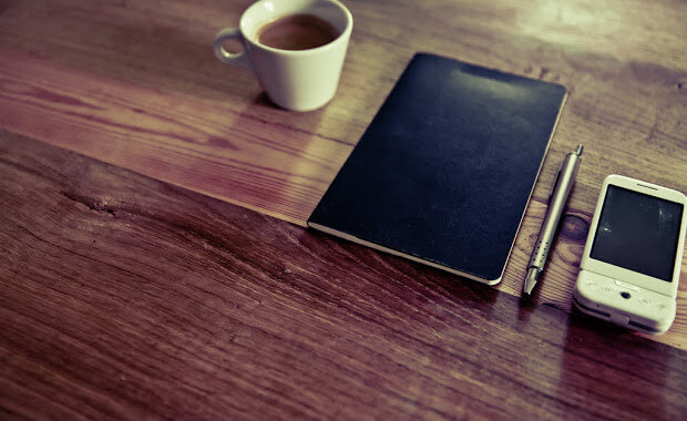 Desk with coffee, tablet, stylus and smart phone